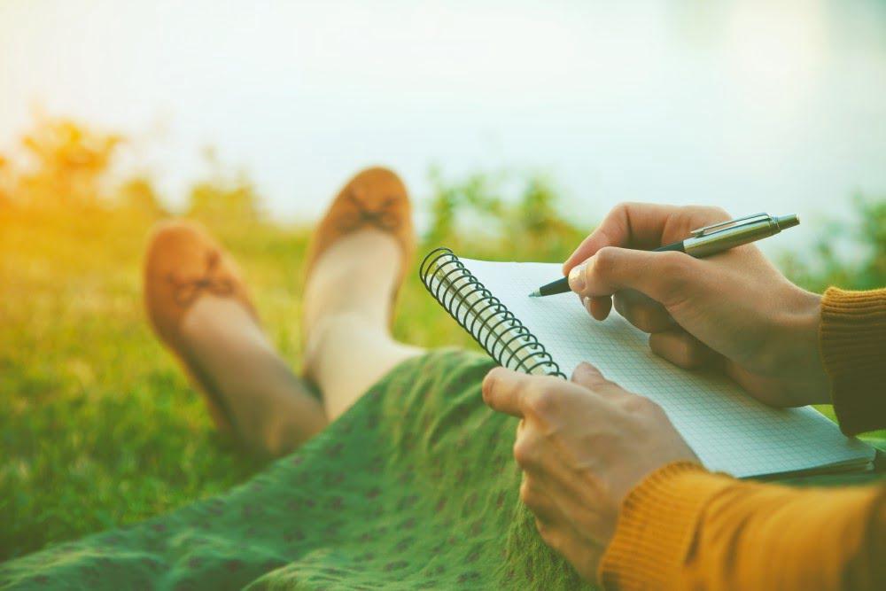 Kvinde der skriver på notesblok